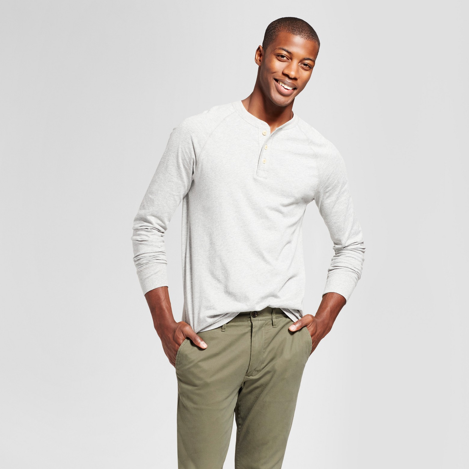 Man wearing white Henley and green pants.