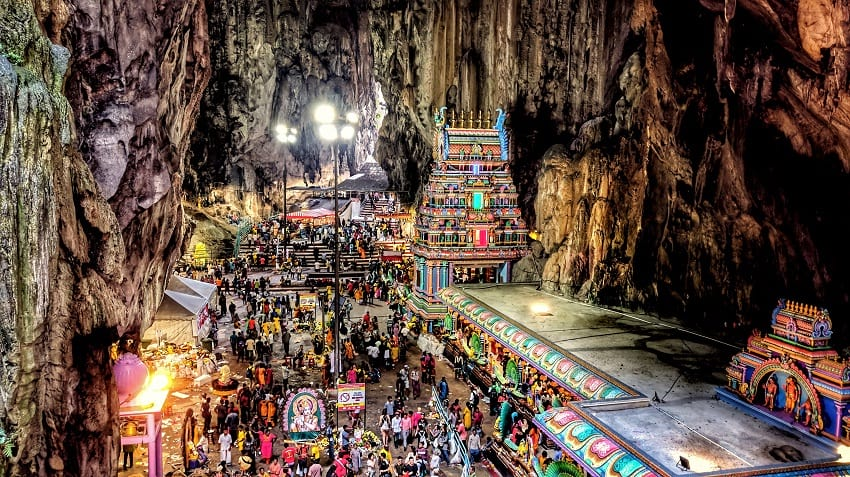 Devotees and tourists inside the Batu Cave temple, witnessing the celebration of Thaipusam festival.