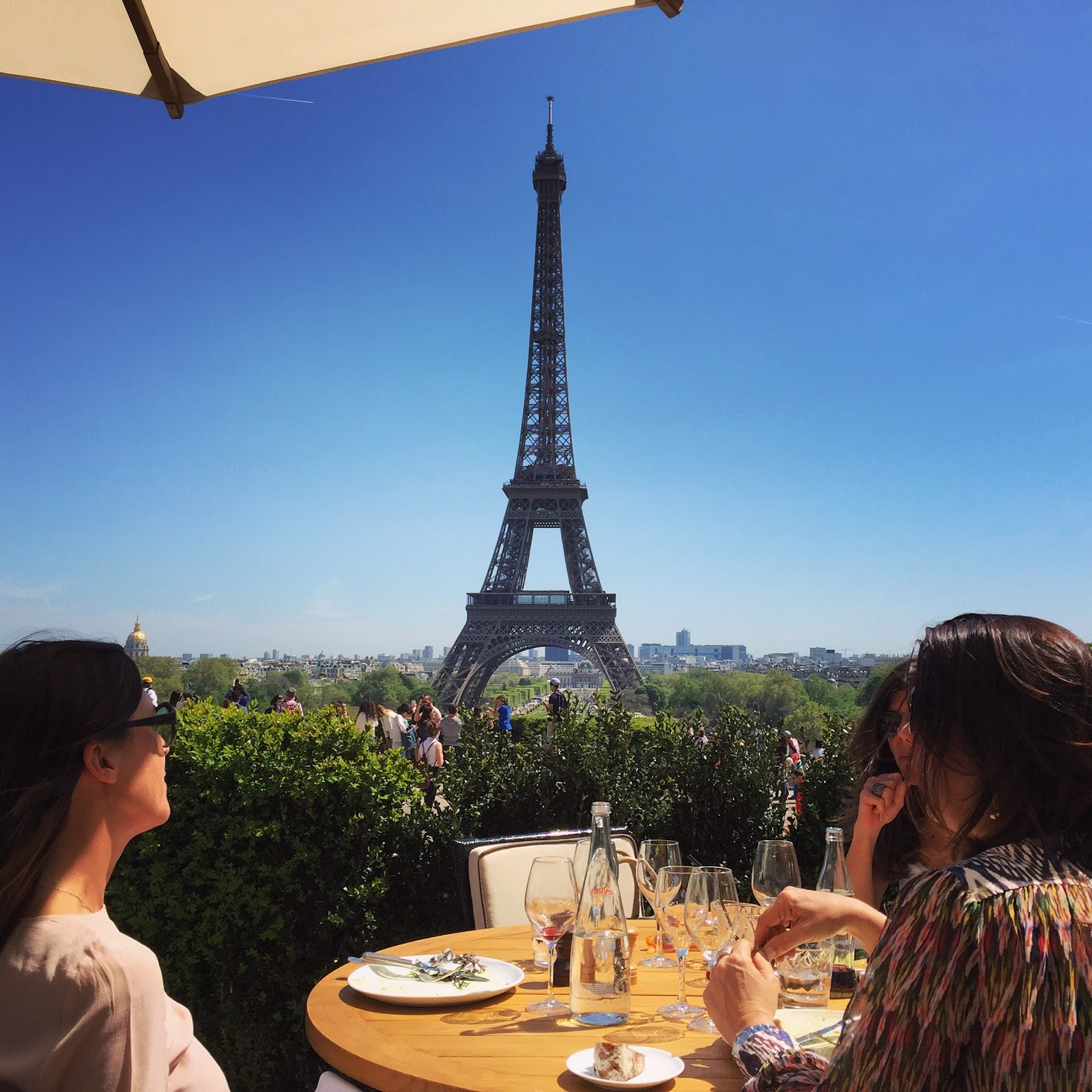 Three young girls enjoying food and drinks served on a wooden table in an outdoor restaurant. Garden terrace overlooking the eiffel tower on a clear, sunny day.