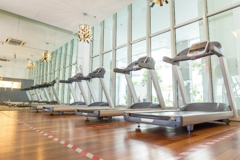 A gym space with gym equipment and pendant lights