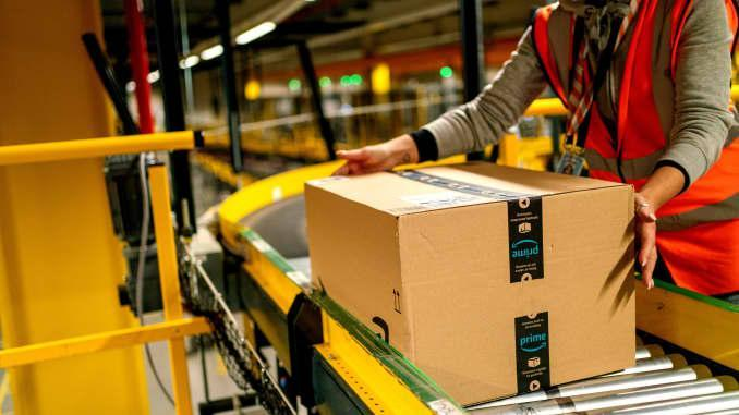A worker collects an Amazon Prime customer order package from a conveyor at an Amazon.com Inc. fulfillment center in Frankenthal, Germany, on Tuesday, Oct. 13, 2020.