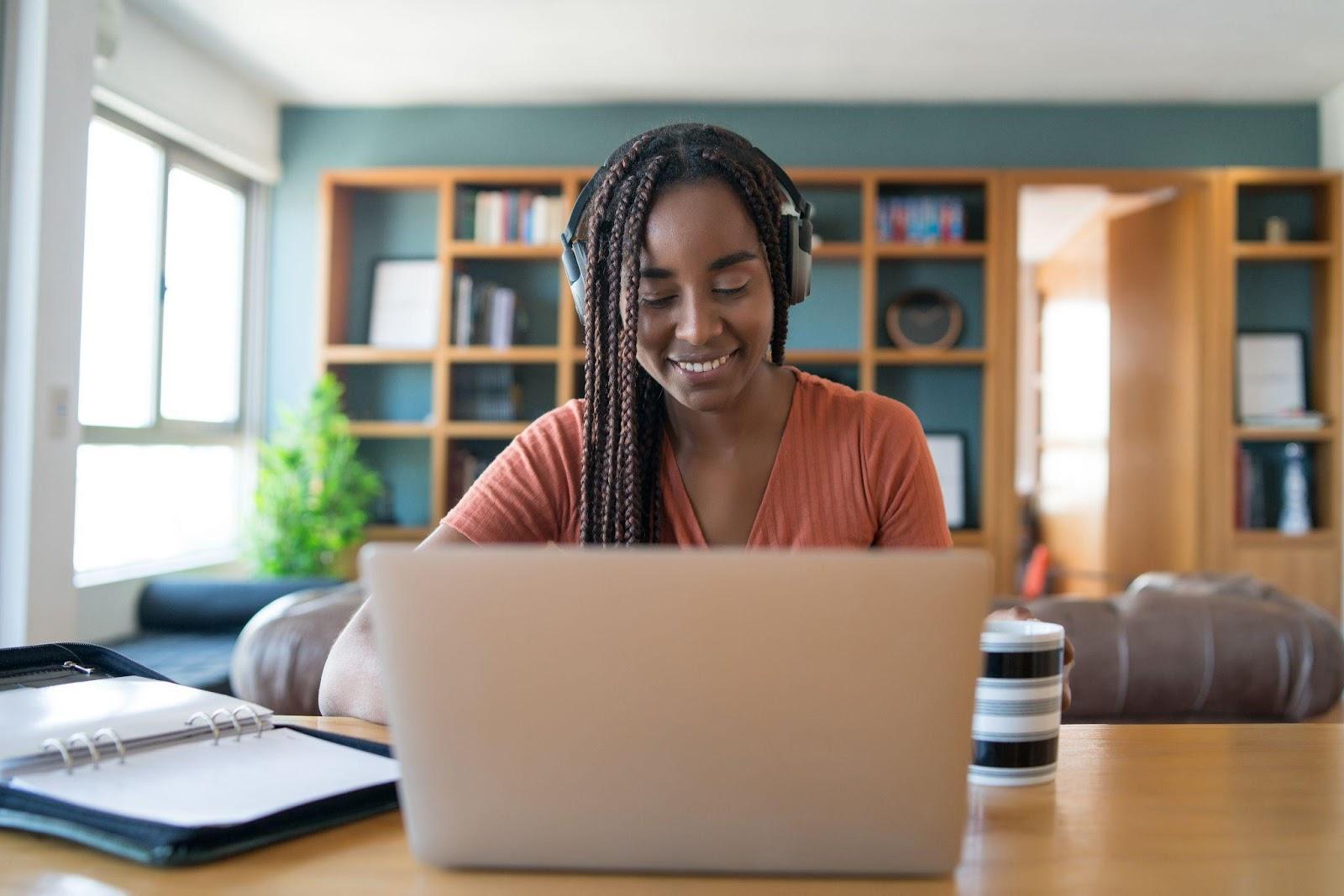 Na imagem há uma mulher negra em frente um notebook trabalhando em home-office.
