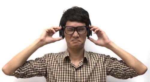 nerdy guy in plaid shirt listening to headphones