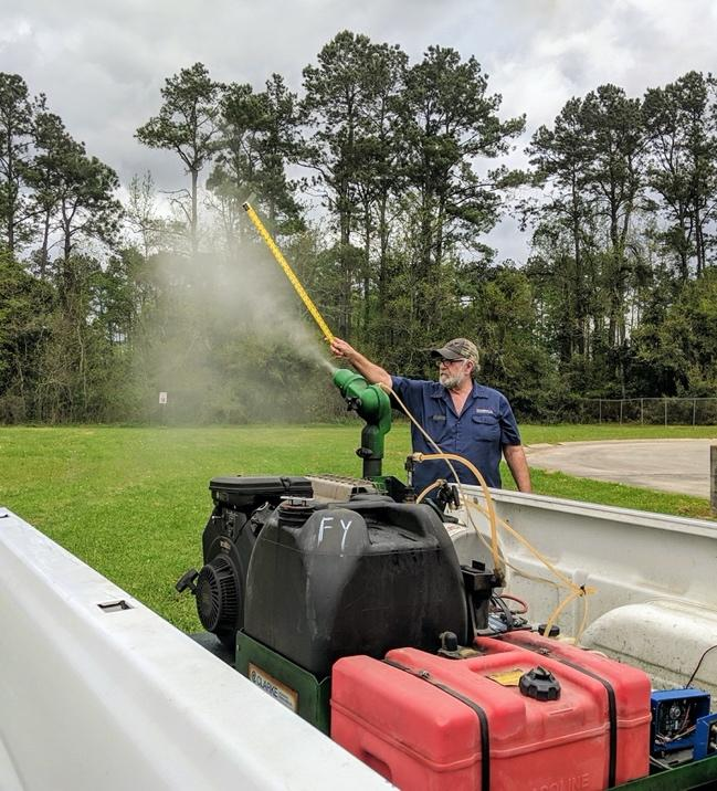 An employee from Tangi Mosquito Abatement measuring the droplets from spray rig