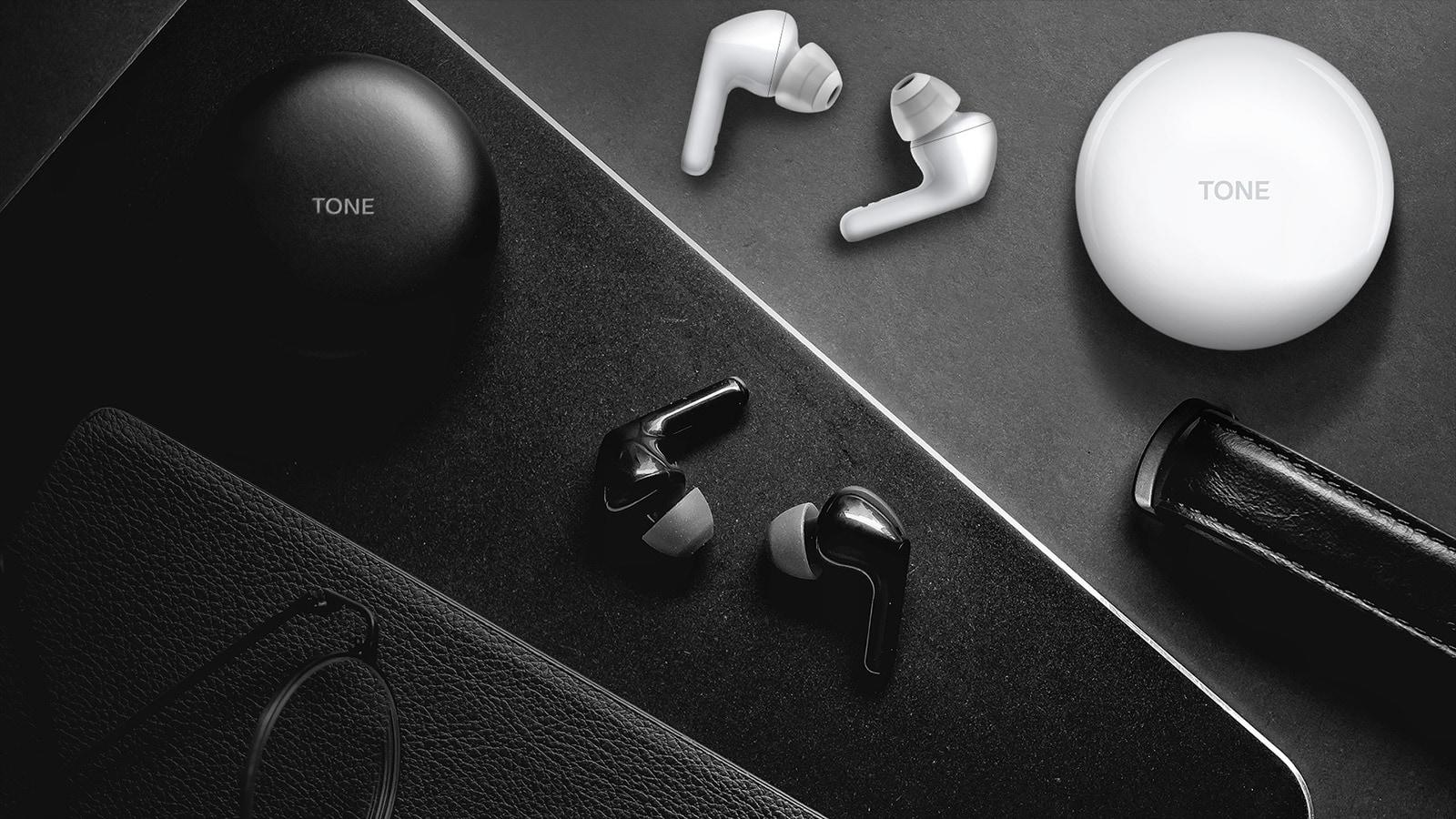 Hình ảnh bên trên của một cái bàn với tai nghe màu đen và màu trắng và hộp tai nghe đặt trên bàn