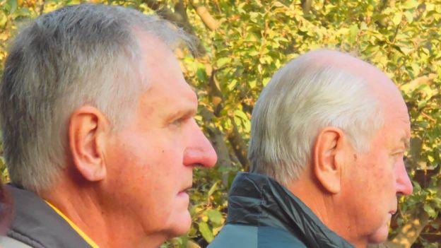 Братья Джеймс (слева) и Даг Дайкс у могилы своих родителей.