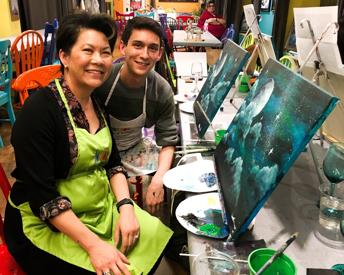 mother and son painting canvases