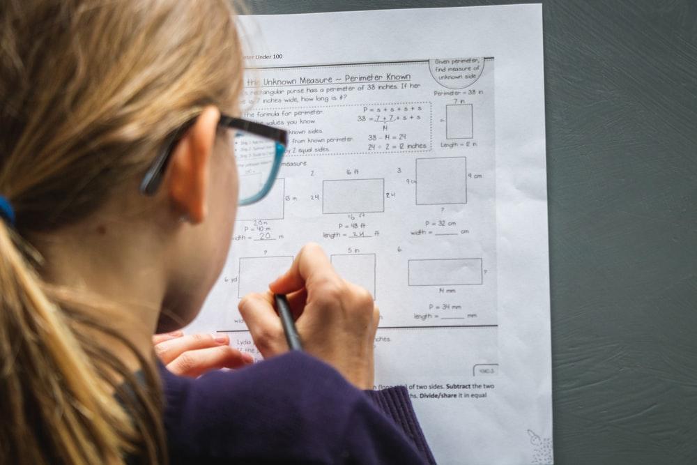 woman in black framed eyeglasses holding pen