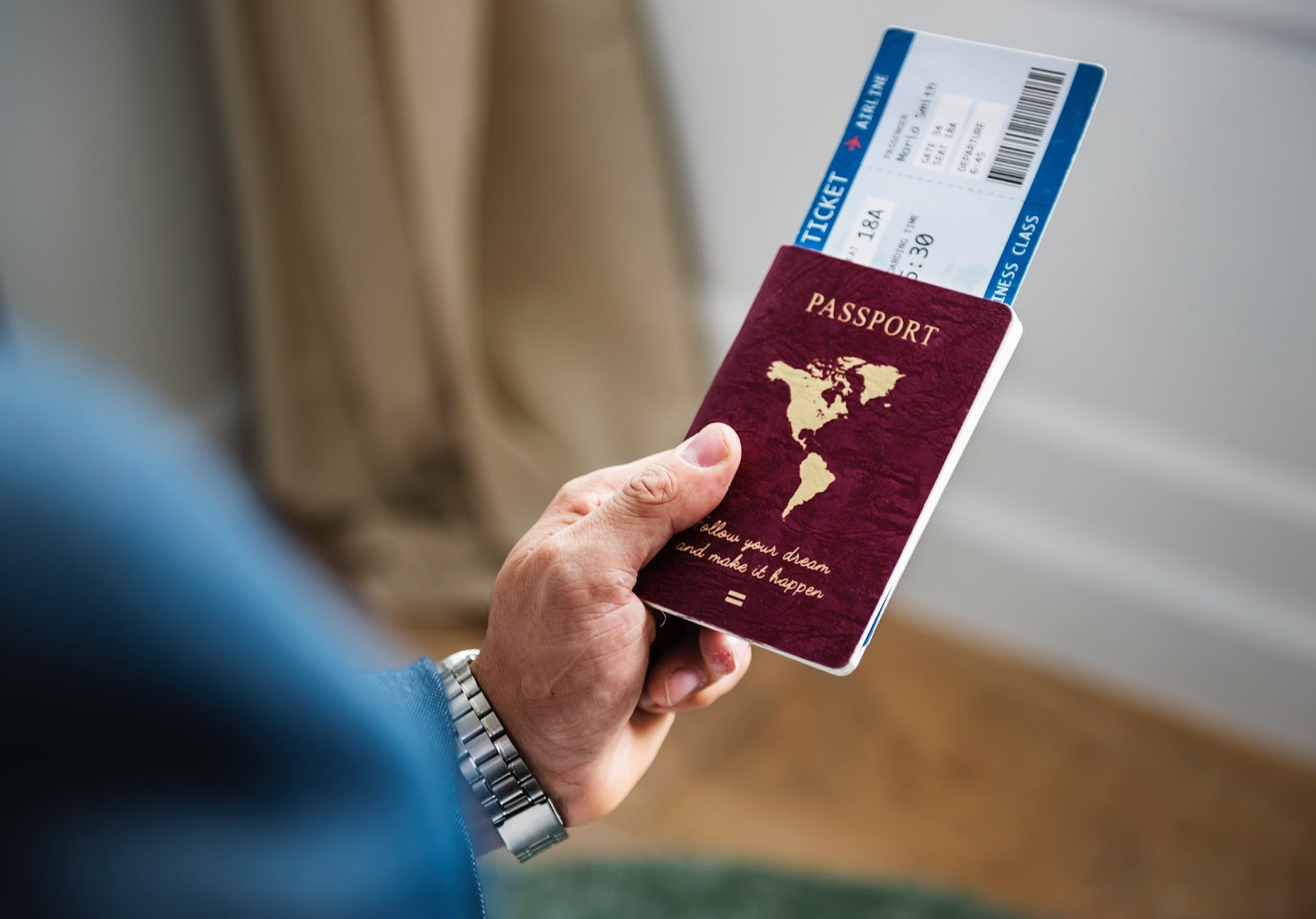 man holding a passport and boarding pass