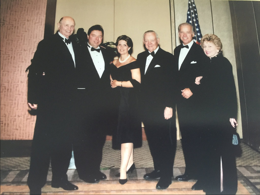 Ed Broyhill pictured in formal attire with former VP Joe Biden and four other individuals.