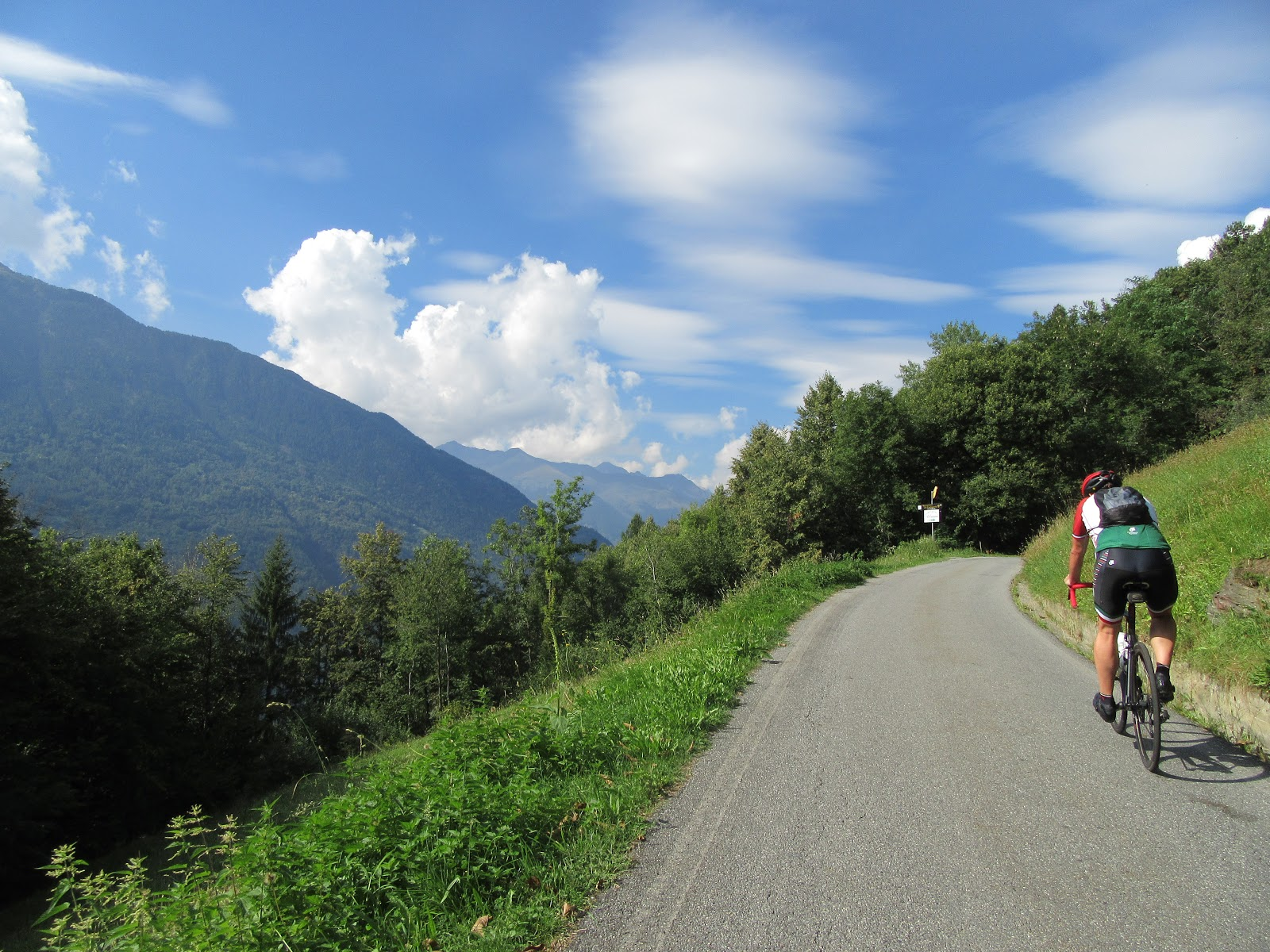 Climbing Passo del Mortirolo from Mazzo di Valtellina by bike - cyclists riding on roadway with mountains and clouds in background