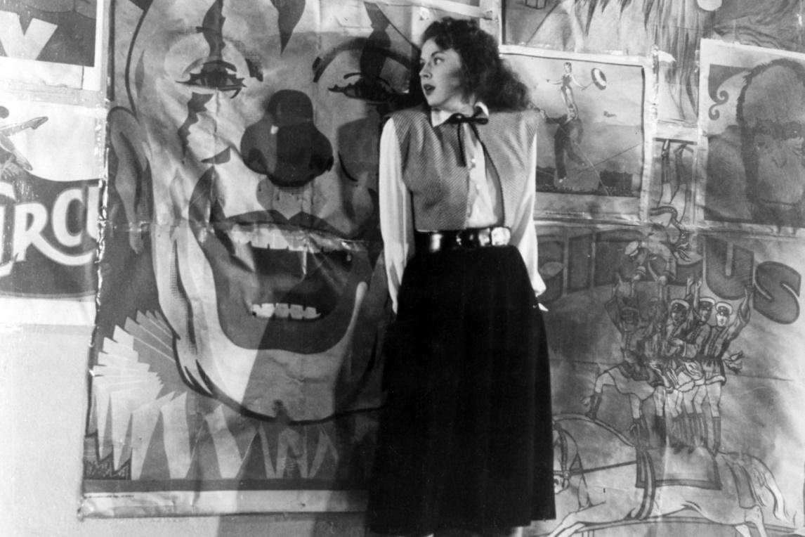 Anne presses her body up against a wall, seemingly trying to hide herself. The wall is papered with circus posters, creating an unsettling backdrop as a huge clown's face is right behind Anne.