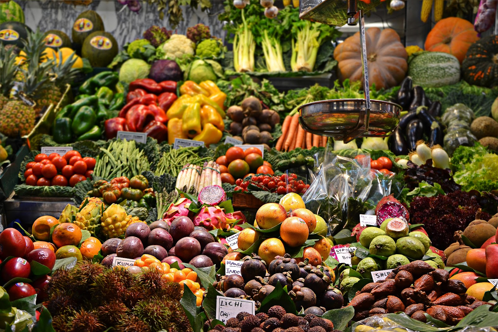 photo of a market stand with multiple types of fruits and vegetables