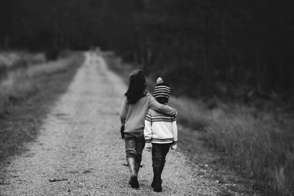 black and white photo of two children walking with arms around each other