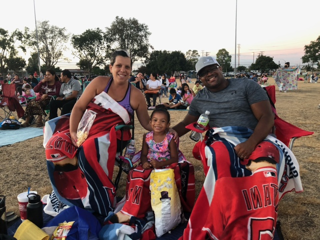 A family of three sits at Rosita Park for Movies in the park. They are each sitting in lawn chairs wrapped in Angels blankets, all three are looking at the camera and smiling.