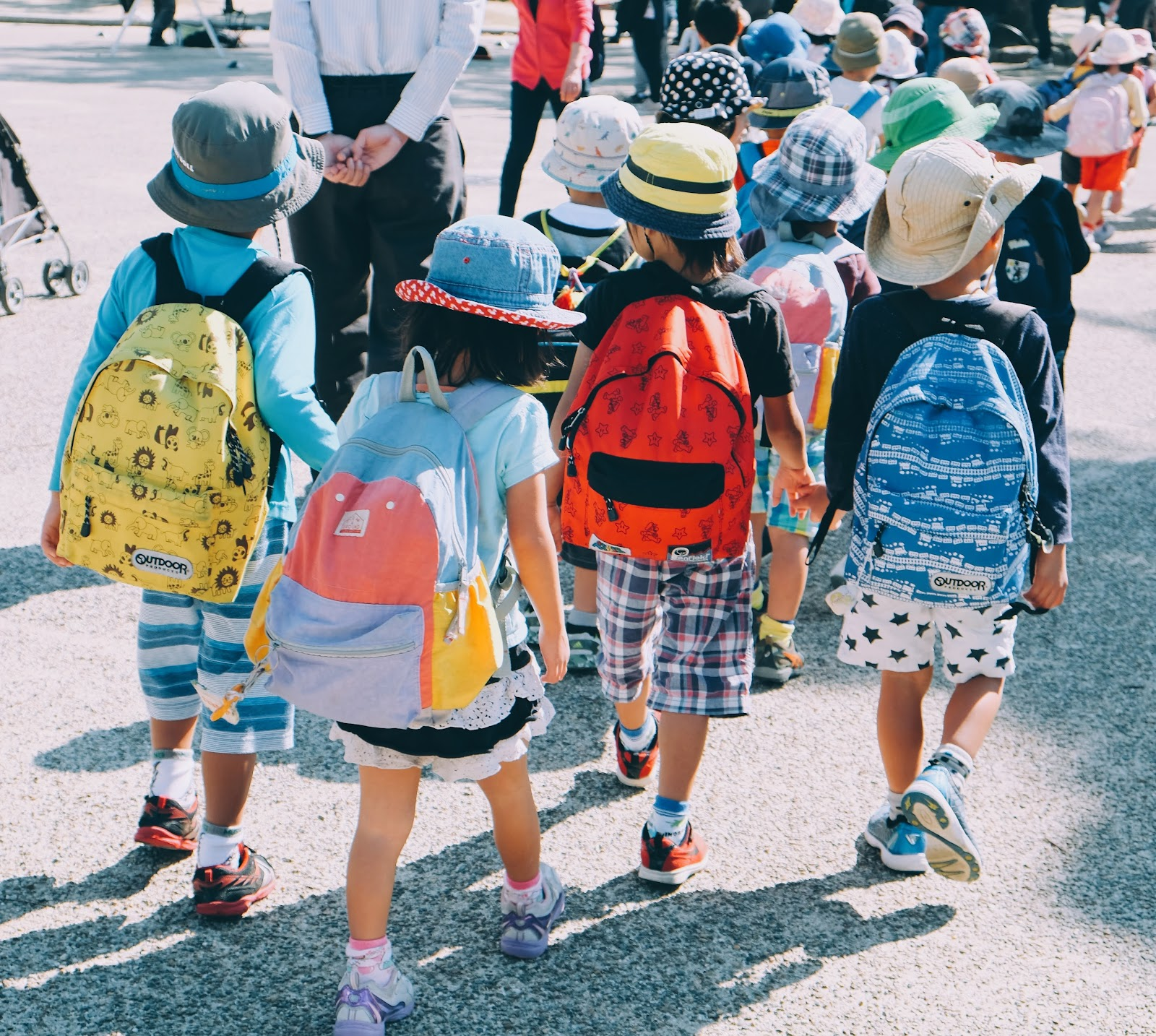 A single file line of elementary students with backpacks travels alongside several teachers.