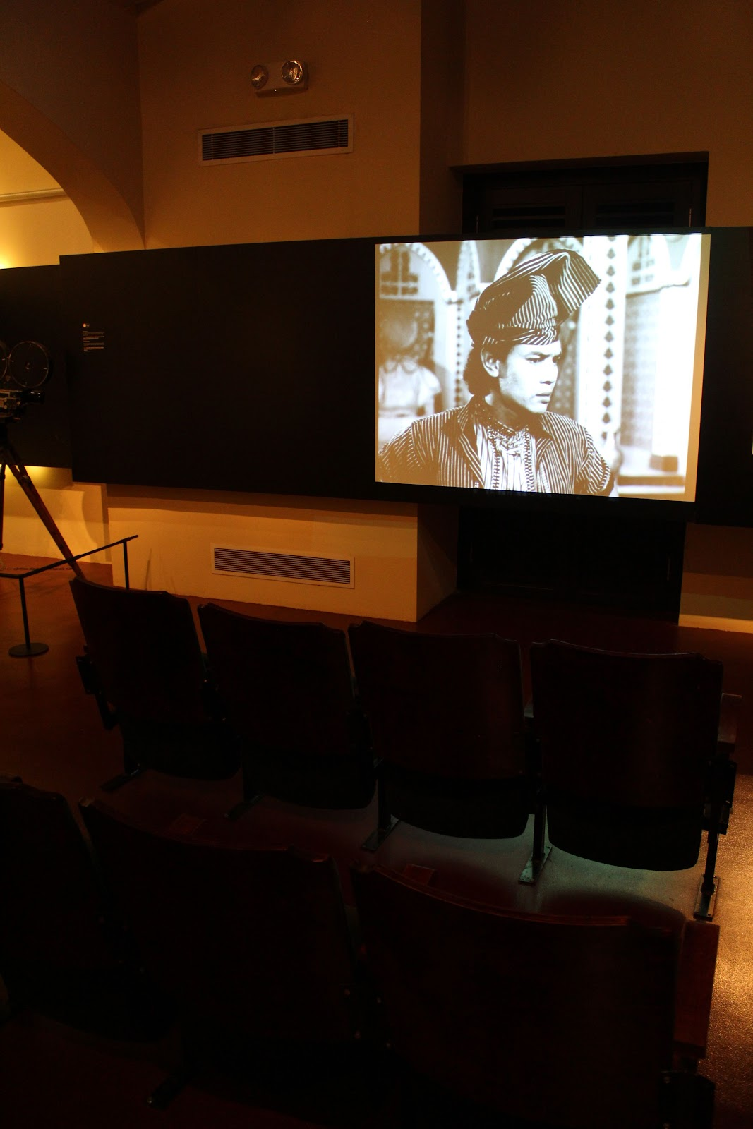 Seating facing a black and white screen, playing an old Malay film
