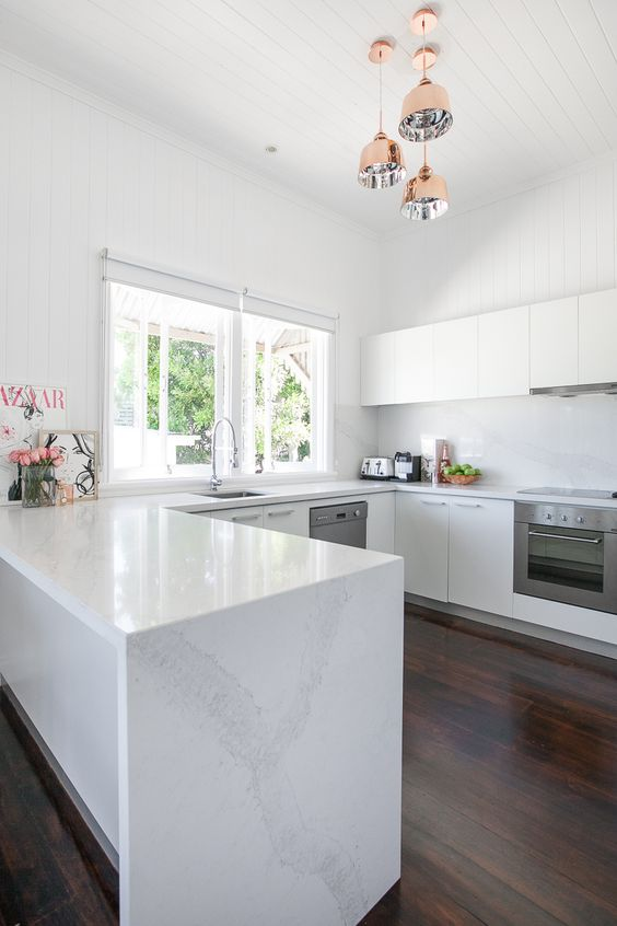 white u-shaped kitchen with flat panel cabinets, dark wood flooring, hanging brass pendant lights and a peninsula with white marble countertops
