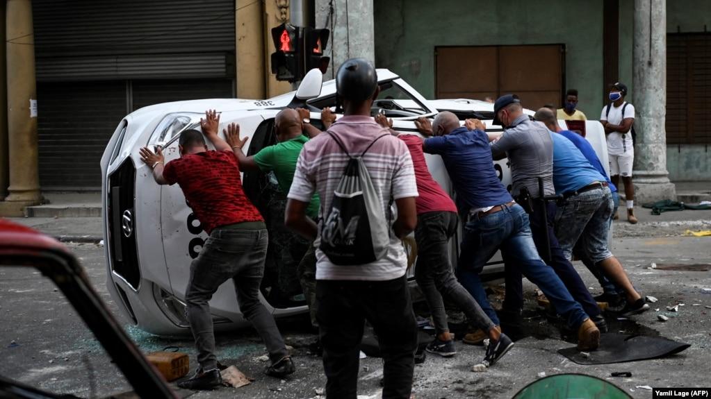 Манифестанты в одном из районов Гаваны переворачивают и разбивают полицейскую автомашину. 11 июля 2021 года