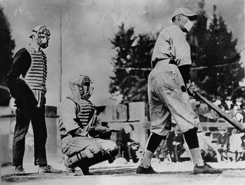 Baseball players, one batting & one catching, and umpire standing behind, wearing masks during the 1918 influenza pandemic