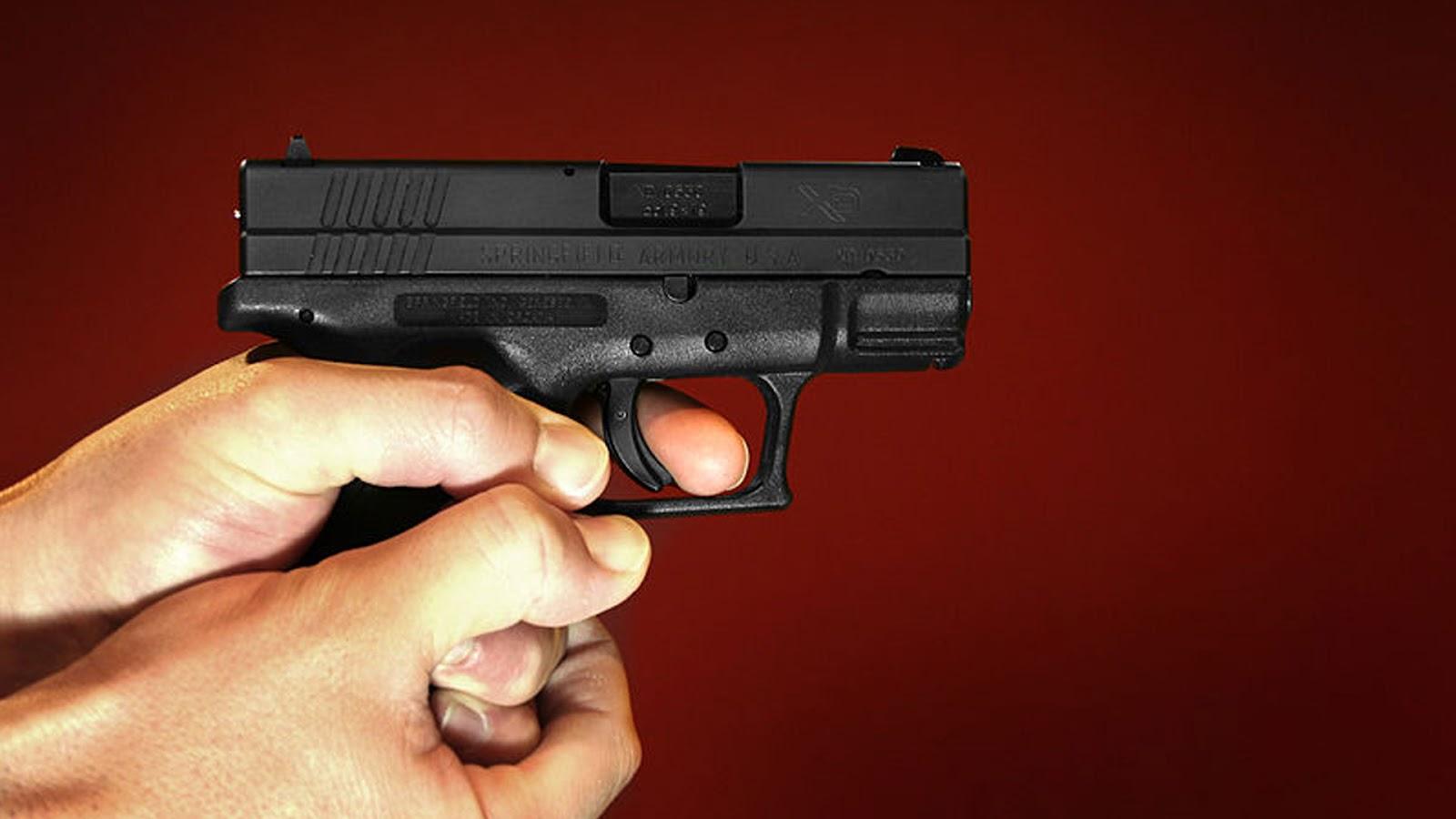 man holding Springfield XD 9mm Handgun with maroon background