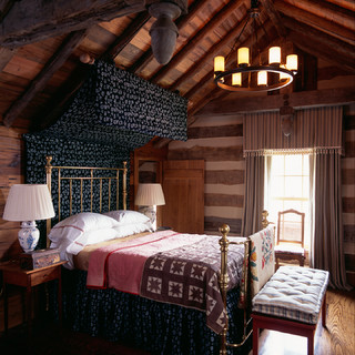 country-style cabin bedroom with canopy, metal bed and tufted bed bench