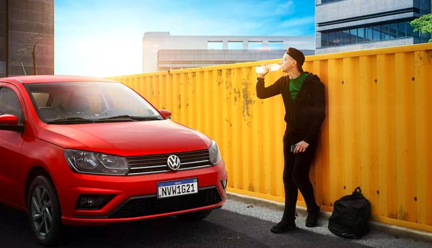 Homem tomando água encostado em uma parede ao lado de um VW Gol vermelho.