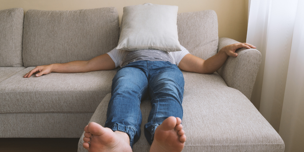 Best travel hacks for men featured by top US travel blog, The Common Traveler: image of a man in jeans on couch with pillow over face
