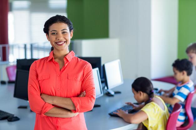 Professora sorri ao ver o resultado positivo de sua formação continuada e ao fundo três crianças utilizam computadores.