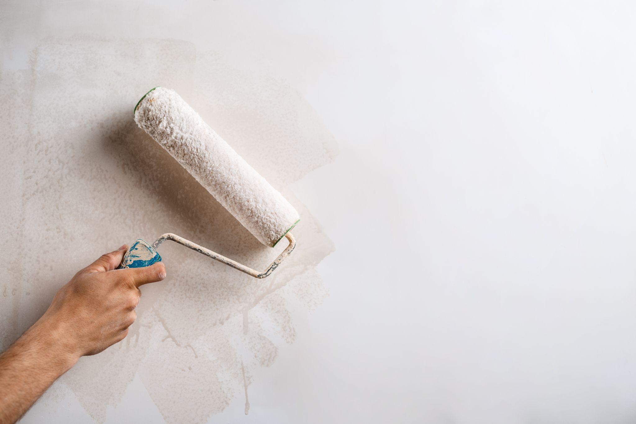 Rolo de pintura pintando parede branca