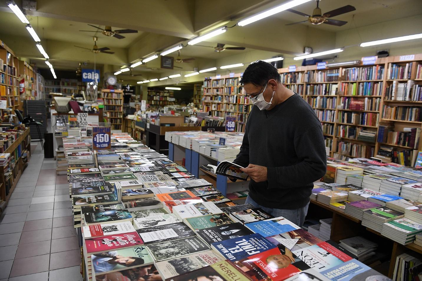 La nueva normalidad. Un hombre con barbijo pasa las hojas de un libro en una librería que reabrió sus puertas a partir de esta mañana