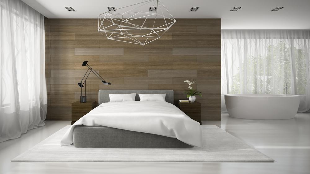 Um quarto minimalista com um pendente geométrico e poucos moveis.
