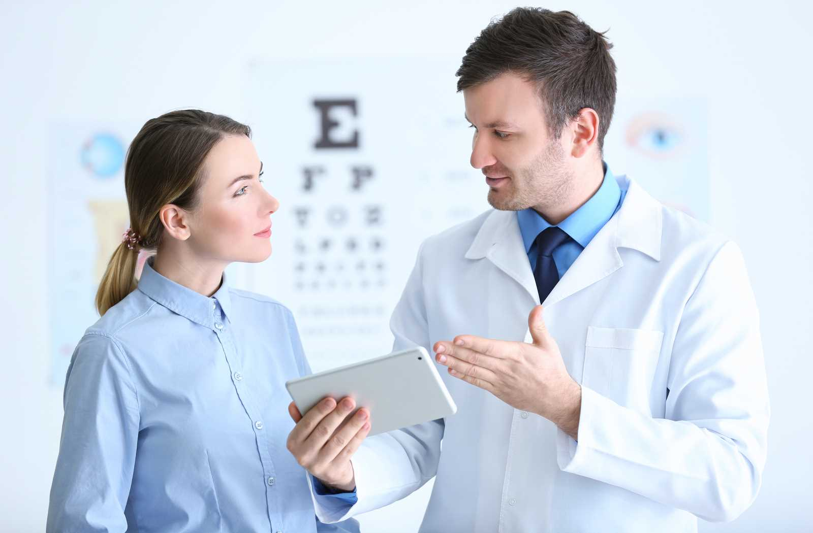 Optometrist explaining how to use eye drops to a patient