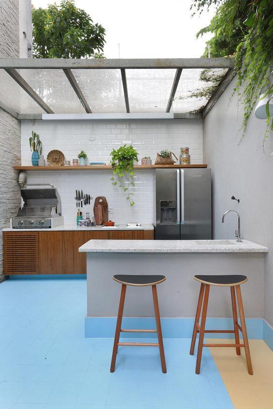 Área externa com parede revestida de azulejo do metrô branco, bancada com churrasqueira a gás, armários de madeira, geladeira de inox, piso azul, bancada de mármore com pia e bancos de madeira.