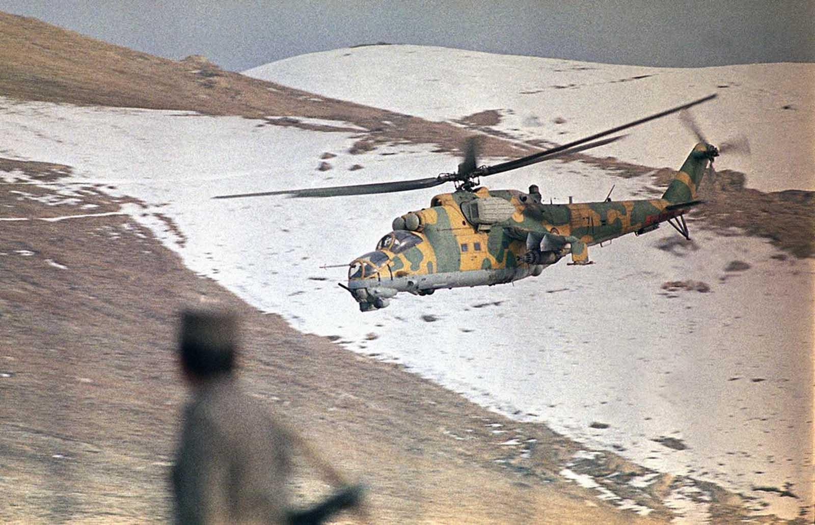 A low-flying Afghan helicopter gunship in snow-capped valley along Salang highway provides cover for a Soviet convoy sending food and fuel to Kabul, Afghanistan, on January 30, 1989. The convoy was attacked by Mujahideen guerrillas with rockets further up the highway, with Afghan government troops returning fire with artillery.