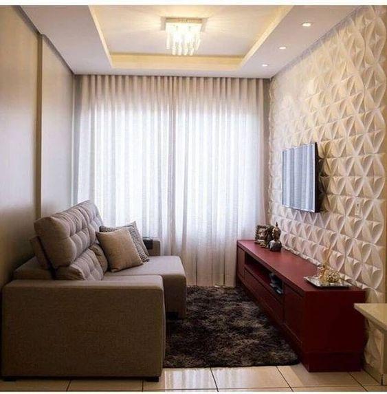 Sala com painel 3D cimentício, sofá bege, hack bordo e cortina longa.