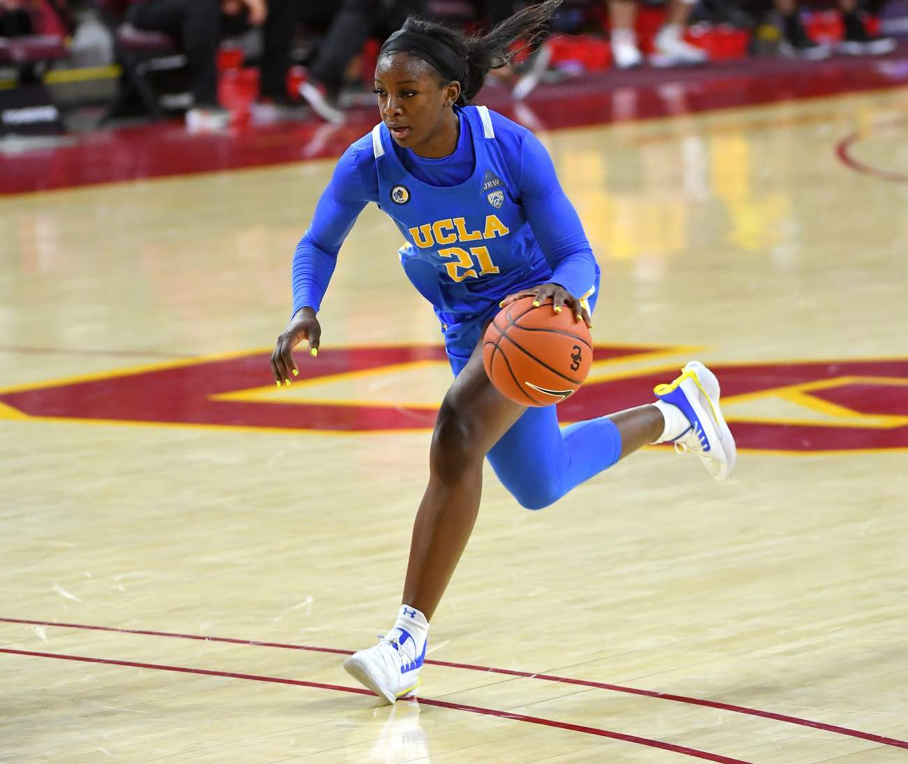 LOS ANGELES, CA - DECEMBER 13: Michaela Onyenwere #21 of the UCLA Bruins takes the ball down court during the game against the USC Trojans at Galen Center on December 13, 2020 in Los Angeles, California. (Photo by Jayne Kamin-Oncea/Getty Images)