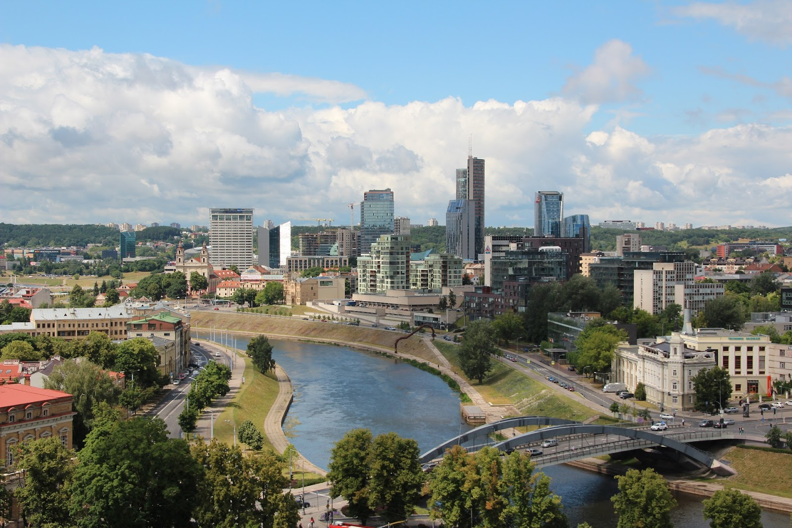 the skyline of vilnius across the river. aerial view, some modern skyscrapers and traditional buildings provide a diverse architectural style. sunny day with some clouds in the distance.
