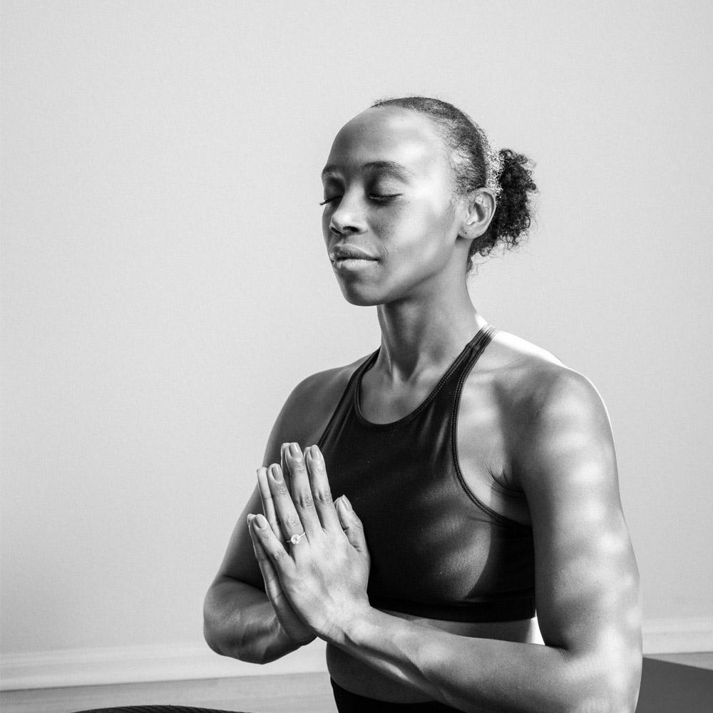 Vrouw aan het mediteren met de ogen dicht in yoga kleding.