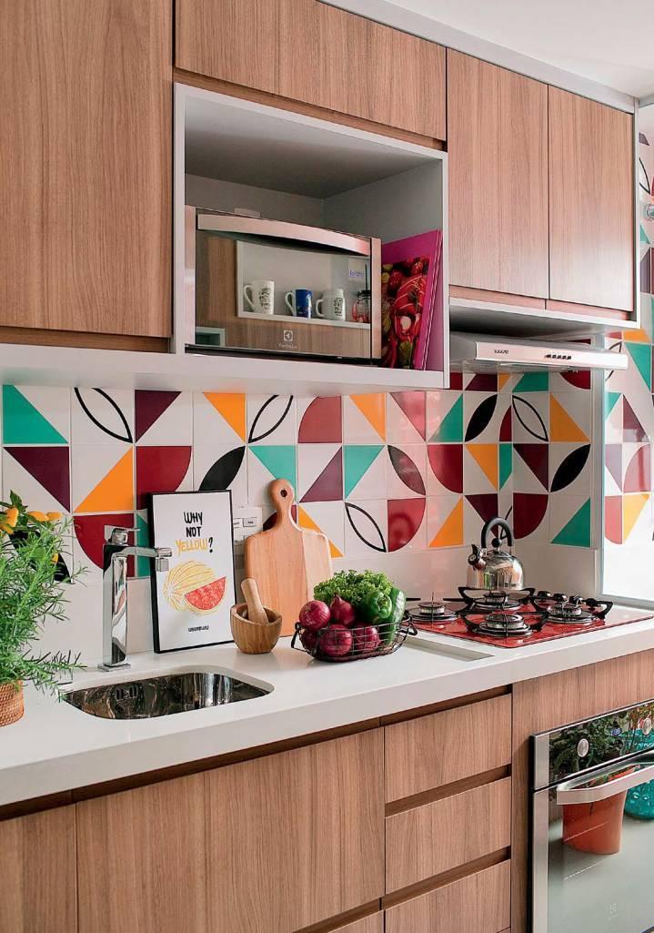 Cozinha com armário de madeira, azulejos geométricos coloridos e utensílios de cozinha.