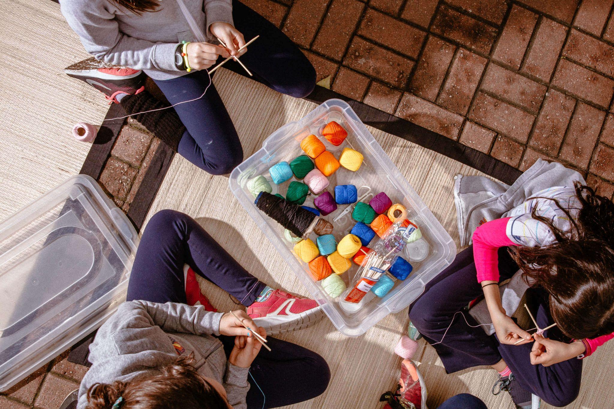 A imagem mostra um grupo de crianças ao redor de uma caixa que contém novelos de linhas coloridas.