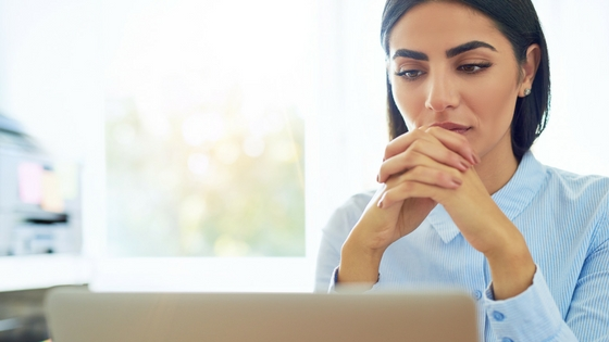 a woman with an open laptop in front of her staring at the screen in a pondering manner