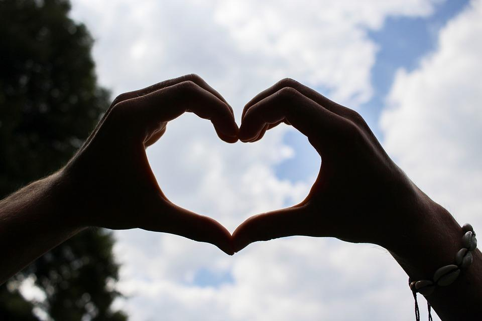 hands making a heart with a cloudy blue background