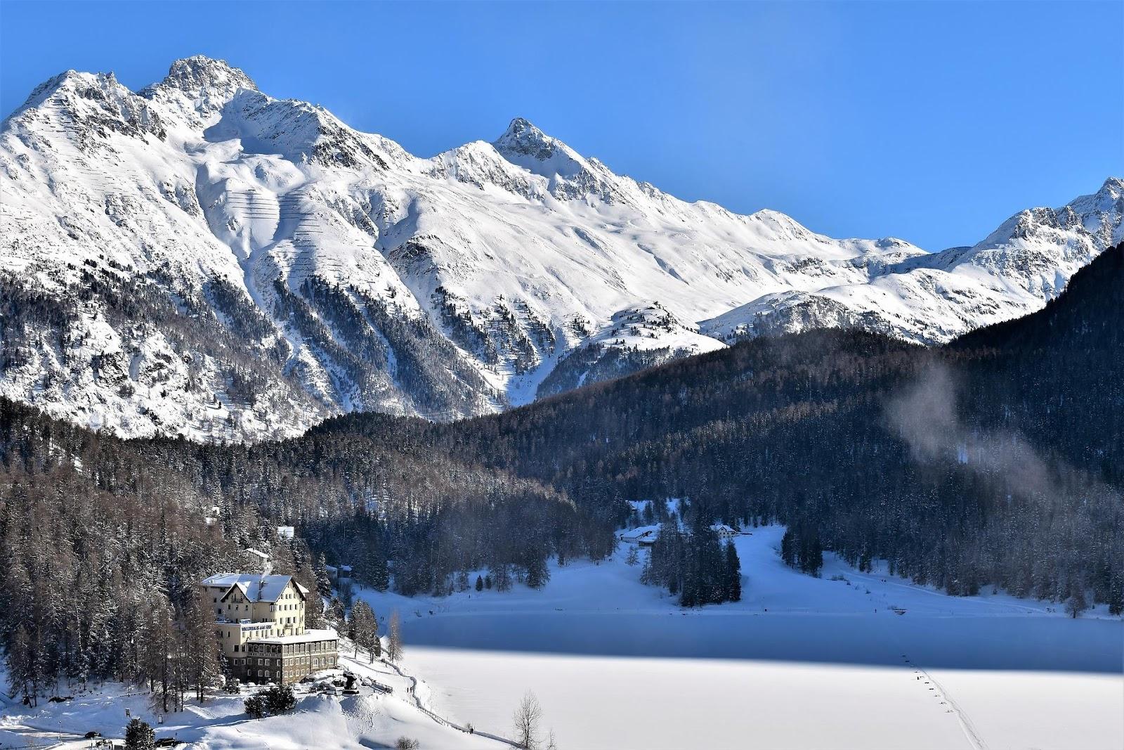 saint moritz ski resort hotel in winter frozen lake alps in background switzerland
