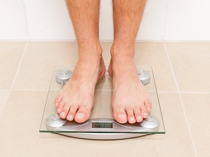 Diabetiker kontrolliert mithilfe einer Personenwaage seinen Gewichtsverlust.