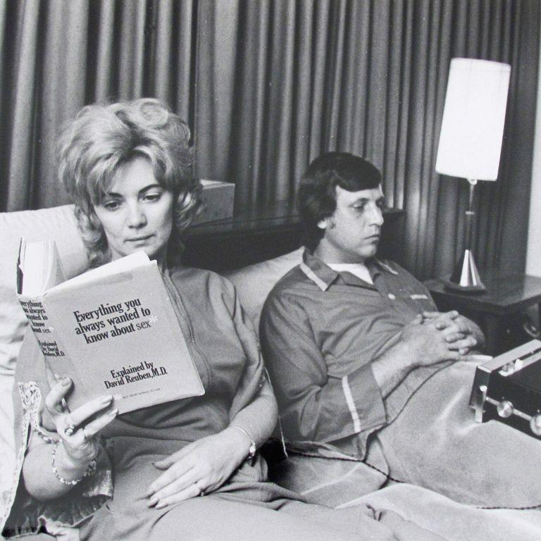 Sieviete lasa grāmatu par seksu, vīrietis klausās radio