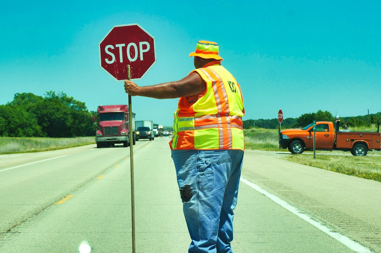 A worker on a highway holds a STOP sign while directing traffic.