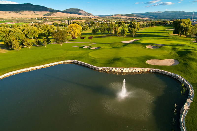 A scenic view above a water feature extending into a fairway with sandtraps and mountains extending into the distance at Kelowna Springs Golf Club on 480 Penno Rd, Kelowna, BC