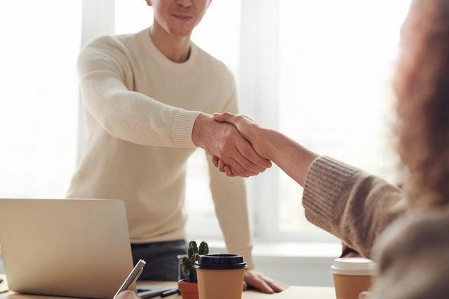 Two people shaking hands  Description automatically generated with low confidence
