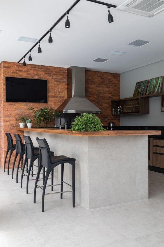 Linda área externa de casa em estilo contemporâneo, com churrasqueira de inox e vidro, parede de tijolinhos, bancada de madeira em estrutura com revestimento imitando cimento queimado e piso também e bancos pretos.
